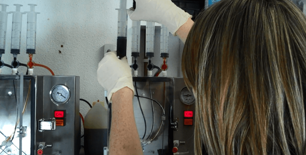 Refilling ink cartridges using a specialist vacuum sealed machine.
